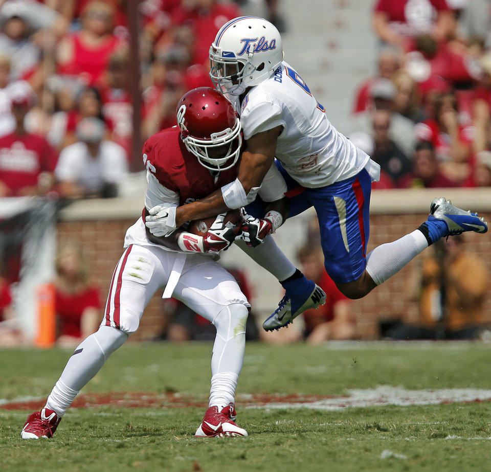 Photo - Oklahoma's Jaz Reynolds (16) makes a catch in front of Tulsa 's Dwight Dobbins (9) during the college football game between the University of Oklahoma Sooners (OU) and the University of Tulsa Hurricanes (TU) at the Gaylord-Family Oklahoma Memorial Stadium on Saturday, Sept. 14, 2013 in Norman, Okla.  Photo by Chris Landsberger, The Oklahoman