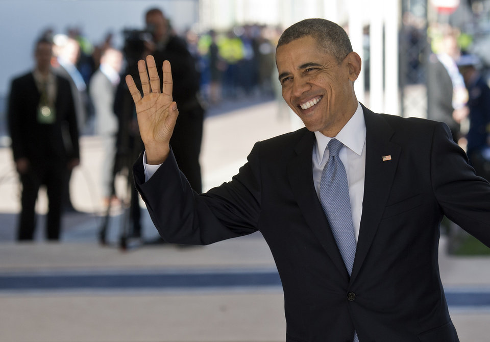 Photo - U.S. President Barack Obama waves as he arrives on the first day of the two-day Nuclear Security Summit (NSS) in The Hague, Netherlands, Monday, March 24, 2014. (AP Photo/Marco de Swart, POOL)