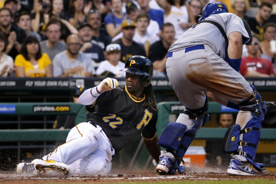 Photo - Pittsburgh Pirates' Andrew McCutchen (22) scores ahead of the tag by Los Angeles Dodgers catcher A.J. Ellis on a single by Pirates' Russell Martin during the fourth inning of a baseball game in Pittsburgh Monday, July 21, 2014. (AP Photo/Gene J. Puskar)
