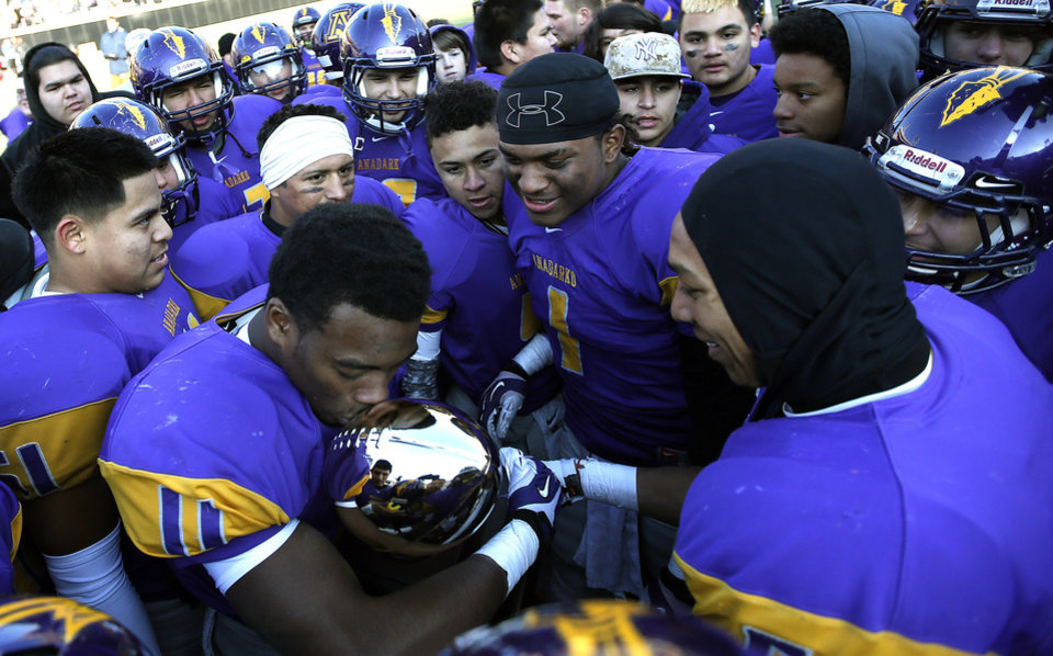 Photo - Anadarko's Mykel Shaw kisses the Championship Trophy following the Class 4A State Football Championship game between Anadarko and Poteau at Boone Pickens Stadium in Stillwater, Okla. Photo by Sarah Phipps, The Oklahoman