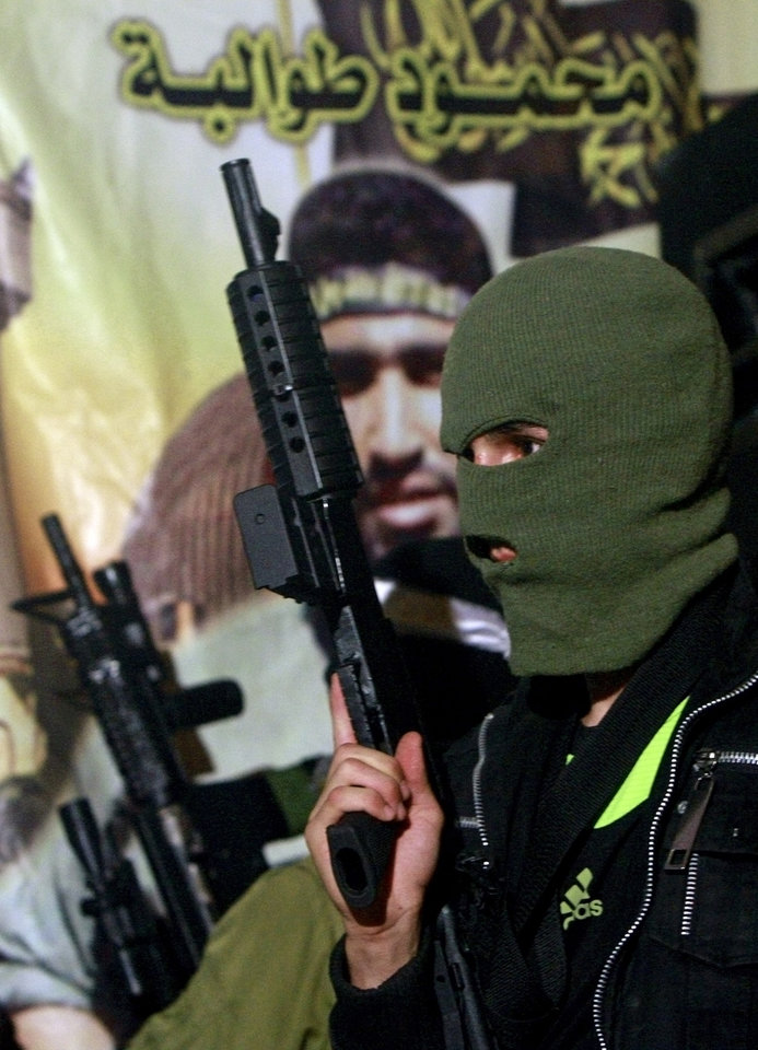 Photo - In this Wednesday, Aug. 20, 2014 Photo, A Palestinian militant holds his weapon during a protest against Israeli operations on the Gaza strip, in the West Bank refugee camp of Jenin. (AP Photo/Mohammed Ballas)