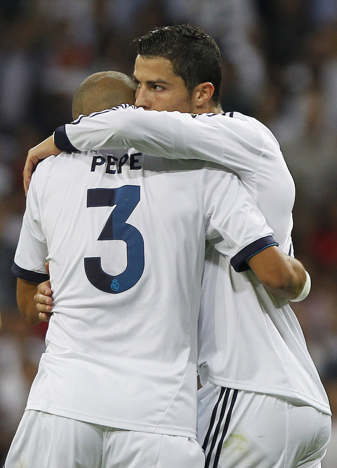 Photo -   Real Madrid's Cristiano Ronaldo from Portugal, right, celebrates his goal with Pepe from Portugal during a Spanish La Liga soccer match against Granada at the Santiago Bernabeu stadium in Madrid, Spain, Sunday, Sept. 2, 2012. (AP Photo/Andres Kudacki)
