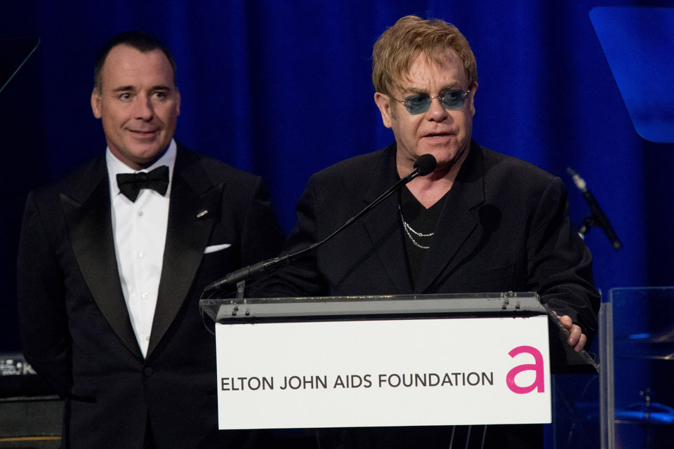Photo -   Elton John, right, and David Furnish appear on stage at Elton John's AIDS Foundation's 11th annual Enduring Vision benefit on Monday, Oct. 15, 2012 in New York. (Photo by Charles Sykes/Invision/AP)