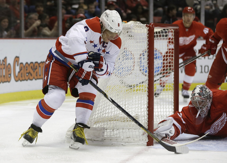 Photo - Detroit Red Wings goalie Jimmy Howard (35) stops a wrap-around attempt by Washington Capitals right wing Alex Ovechkin (8) during the first period of an NHL hockey game in Detroit, Friday, Jan. 31, 2014. (AP Photo/Carlos Osorio)
