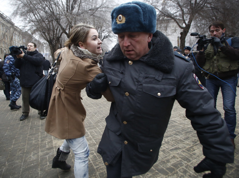 Photo - Police officers detain people who gathered for an unsanctioned event in downtown Volgograd, Russia, Monday, Dec. 30, 2013. A bomb blast tore through a trolleybus in the city of Volgograd on Monday morning, killing at least 10 people. a day after a suicide bombing that killed at least 17 at the city's main railway station. Volgograd is about 650 kilometers (400 miles) northeast of Sochi, where the Olympics are to be held. (AP Photo/Denis Tyrin)