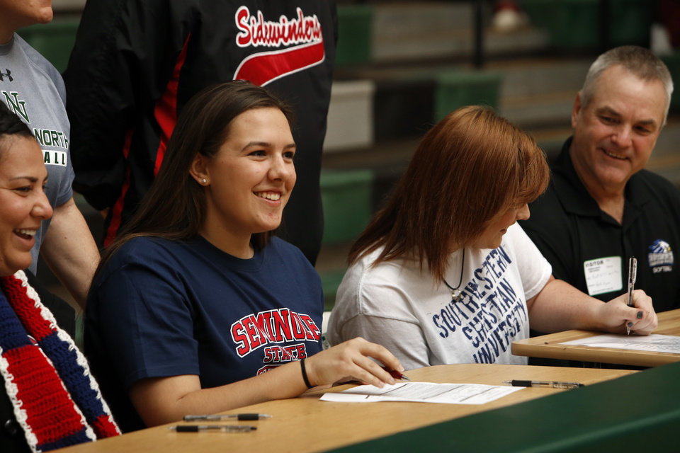 Photo - Morgan Wardlow, left,  signs to play softball at Seminole State University and Katelyn Dollard signs with Southwest Christian at a signing day assembly at Norman North High School on Wednesday, Feb. 6, 2013, in Norman, Okla.  Photo by Steve Sisney, The Oklahoman