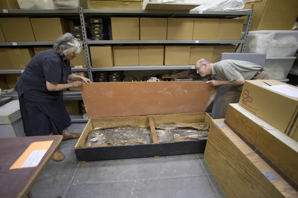 Photo - Janet Monge, the curator-in-charge of the anthropology section at the The Penn Museum, part of the University of Pennsylvania, and William Hafford, manager of the Ur digitization project open a container of recently rediscovered 6,500-year-old human  remains during an interview with The Associated Press Tuesday, Aug. 5, 2014, in Philadelphia. The museum announced Tuesday that it had rediscovered in its own storage rooms a 6,500-year-old human skeleton believed to have been a man at least 50 who stood 5 feet, 9 inches tall. The remains were originally excavated from southern Iraq around 1930.(AP Photo/Matt Rourke)
