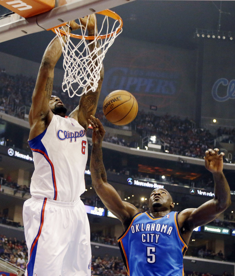 Photo - Los Angeles Clippers center DeAndre Jordan (6) dunks over Oklahoma City Thunder center Kendrick Perkins (5) in the first half of an NBA basketball game in Los Angeles, Sunday, March 3, 2013. (AP Photo/Reed Saxon) ORG XMIT: LAS102