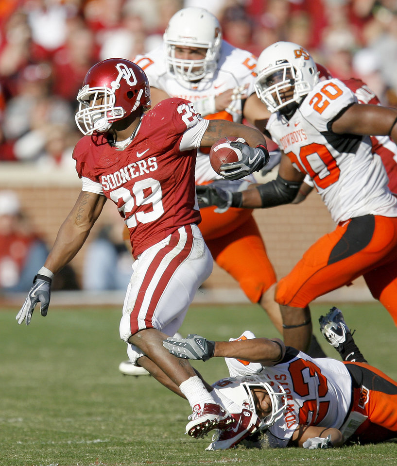 Photo - OU's Chris Brown runs over OSU's Terrance Anderson during the second half of the Bedlam college football game between the University of Oklahoma Sooners (OU) and the Oklahoma State University Cowboys (OSU) at the Gaylord Family-Oklahoma Memorial Stadium on Saturday, Nov. 28, 2009, in Norman, Okla.Photo by Bryan Terry, The Oklahoman