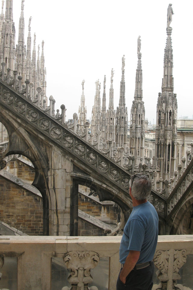 Photo - This July 6, 2012 photo shows a man looking at the spires of the Milan cathedral in Milan, Italy. To travel through northern Italy with a copy of Mark Twain's 1869 ''The Innocents Abroad', his classic 'record of a pleasure trip'. It took him to the great sights of Europe and on to Constantinople and Jerusalem before he sailed home to New York. Such a trip would take far too big a chunk out of my holiday time. But, Milan, Florence and Venice, a mere fragment for Twain, was within my reach for a two-week vacation. (AP Photo/Raf Casert)