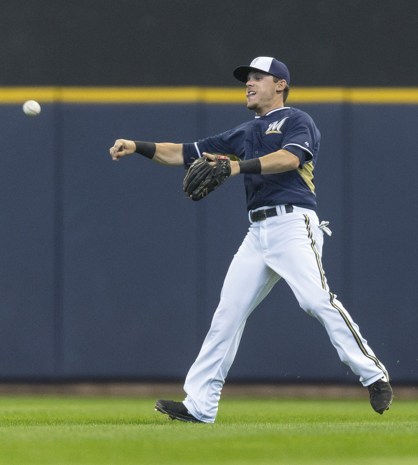 Photo - Milwaukee Brewers' Scooter Gennett makes a throw to second against the Kansas City Royals during the second inning of an exhibition baseball game Saturday, March 29, 2014, in Milwaukee. (AP Photo/Tom Lynn)