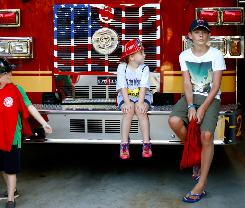 Photo -  Cancer patient Sam Oliver, 13, from London, sits beside Peyton Dugger, 6, from Hollis, Okla., as they wait for a group photo on a Warr Acres fire truck, Wednesday, July 24, 2013. Peyton is caner patient Jaxon Dugger's sister. Photo by Bryan Terry, The Oklahoman