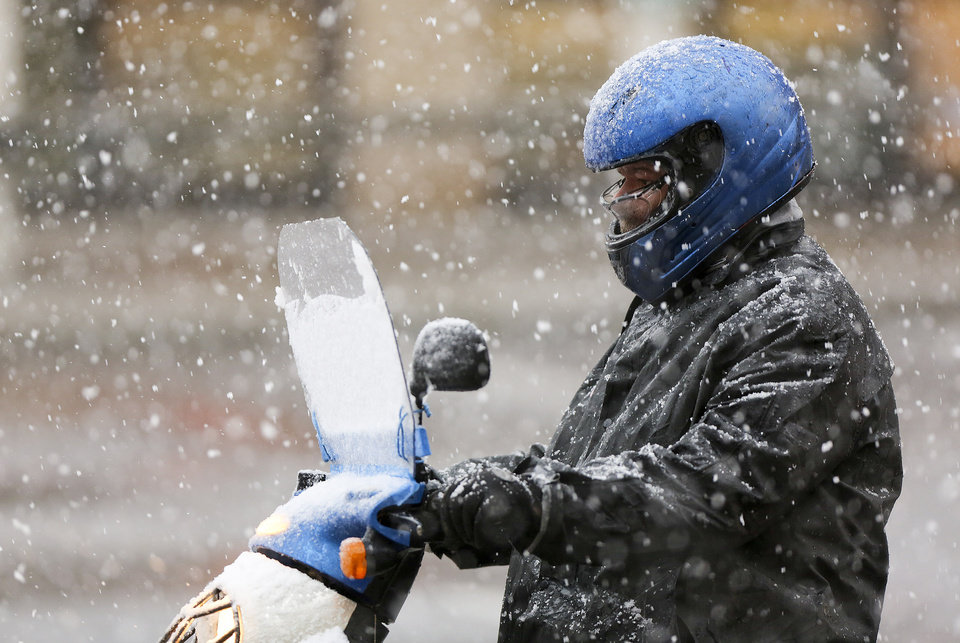 Photo - A commuter on a moped heads down Campbell Avenue in heavy snow on Thursday afternoon Jan. 17, 2013 in Roanoke, Va.   Virginia is bracing for the first significant snowstorm of the winter season.  Photo taken 1/17/2013 (AP PHOTO/The Roanoke Times, Kyle Green)