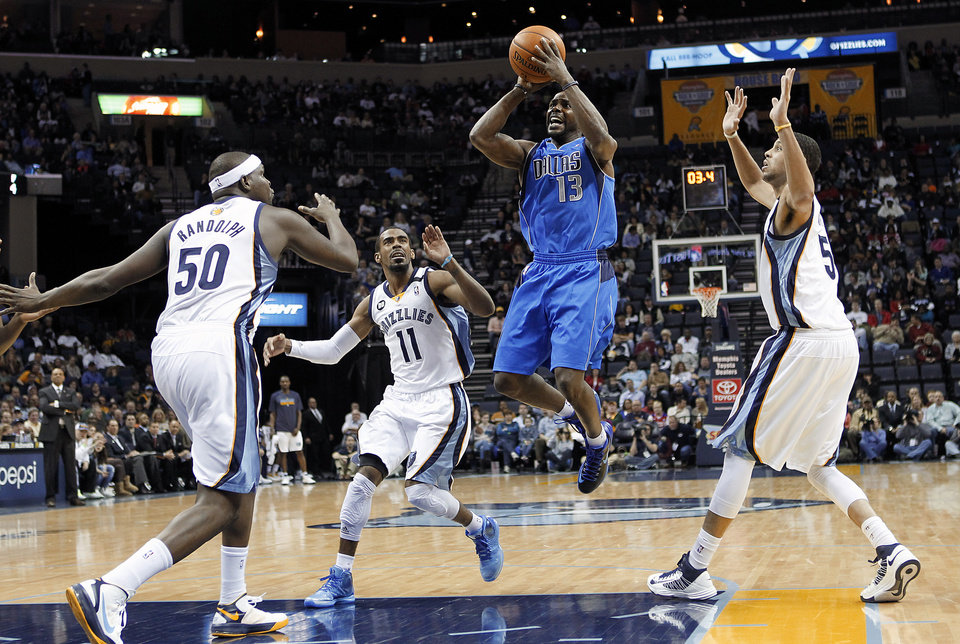 Photo - Dallas Mavericks guard Mike James (13) goes to the basket against Memphis Grizzlies' Zach Randolph (50), Mike Conley (11) and Austin Daye (5) during the first half of an NBA basketball game Wednesday, Feb. 27, 2013, in Memphis, Tenn. (AP Photo/Lance Murphey)
