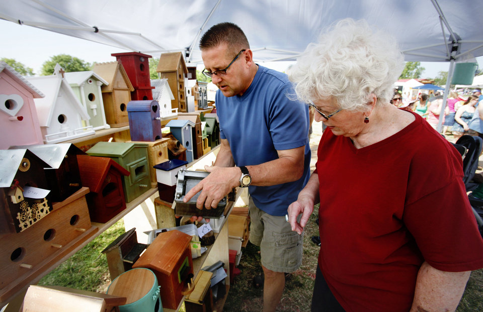 Photo - Birdhouse craftsman Thomas Mack shows his wares to Sharon Sala at the annual May Fair Festival on Saturday at Andrews Park in Norman.