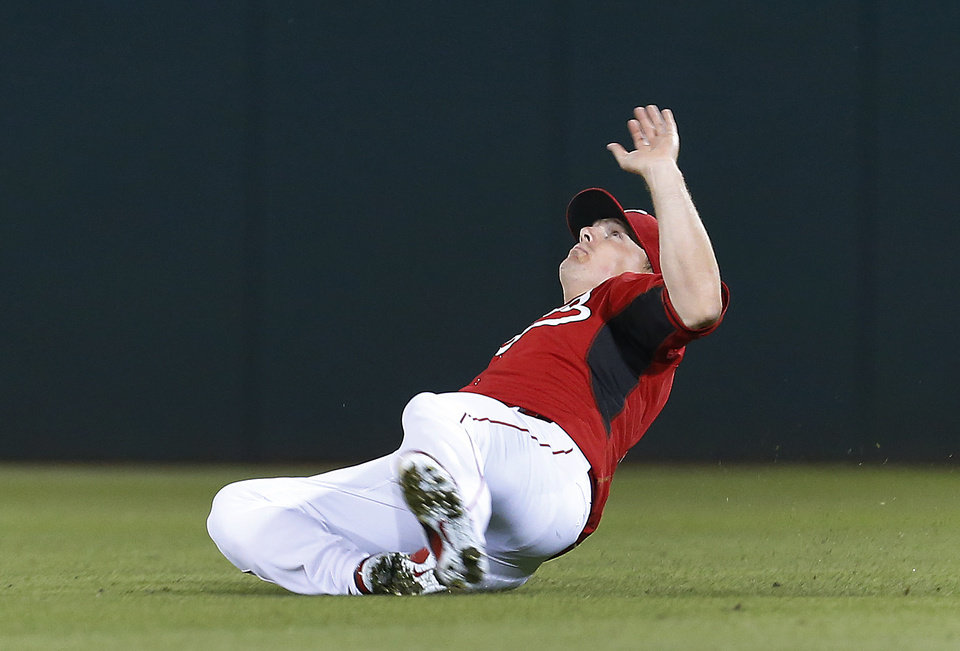 Photo - Cincinnati Reds right fielder Jay Bruce slips in the outfield on a Los Angeles Dodgers' Juan Uribe pop fly in the fifth inning during an exhibition baseball game in Goodyear, Ariz., Wednesday, March 5, 2014. Uribe ended up with a single. (AP Photo/Paul Sancya)
