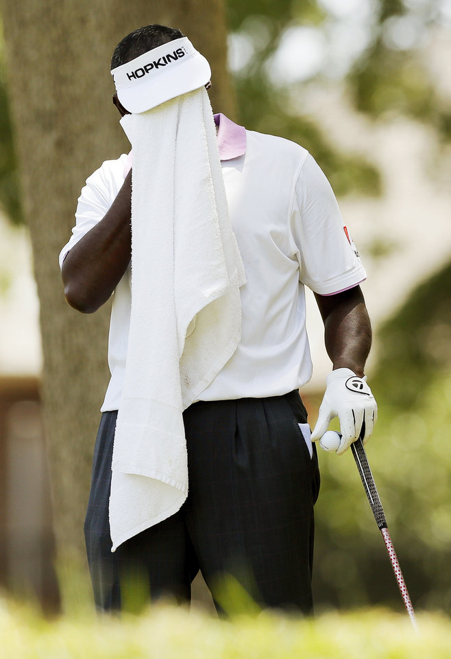 Photo - Vijay Singh wipes his face before his tee shot on No. 5 during the third round of the U.S. Senior Open golf tournament at Oak Tree National in Edmond, Okla., Saturday, July 12, 2014. Photo by Nate Billings, The Oklahoman