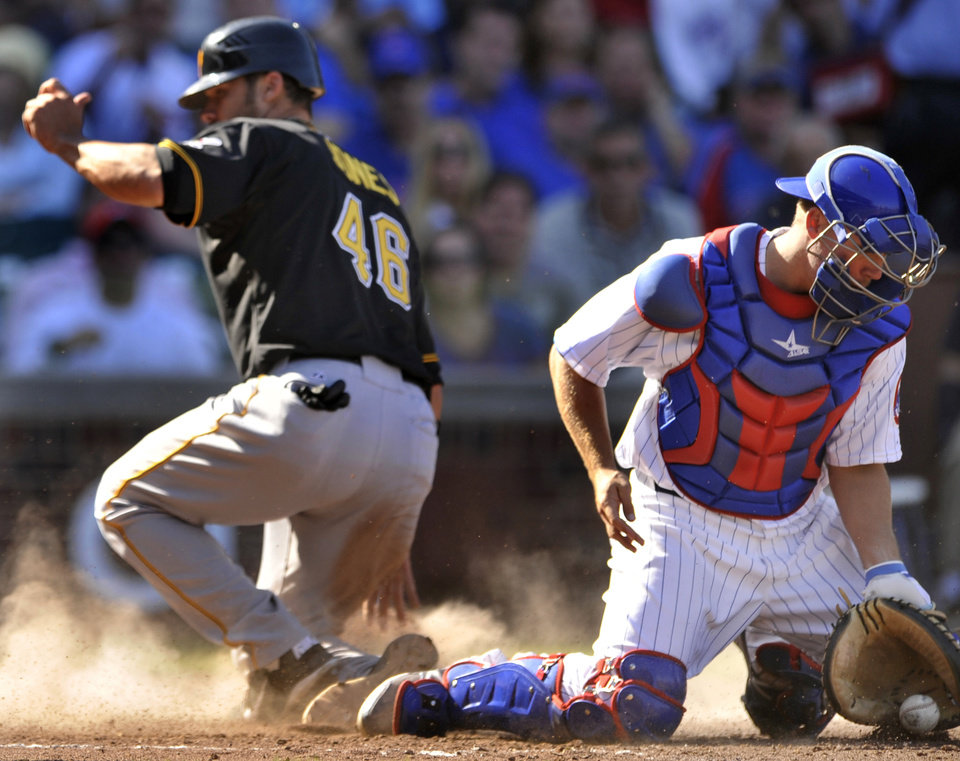 Photo -   Chicago Cubs catcher Steve Clevenger right, stops the ball as Pittsburgh Pirates' Garrett Jones slides into home plate safely after Pedro Alvarez grounded out in the sixth inning during a baseball game in Chicago, Friday, Sept. 14, 2012. (AP Photo/Paul Beaty)