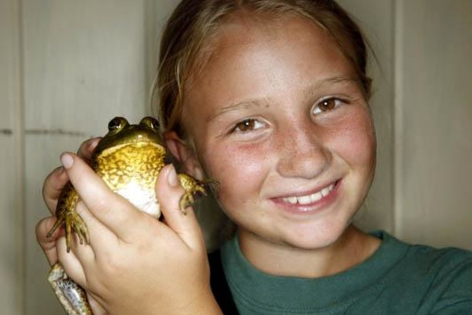 Photo -  Kylie Moates, 9, poses with a bull frog after the frog and turtle races, Wednesday, June 24, 2009, at  Camp DaKaNi in Oklahoma City. Photo by Sarah Phipps, The Oklahoman