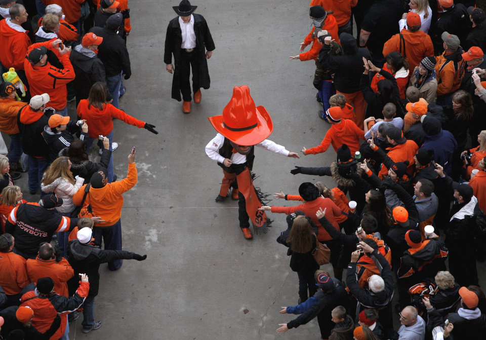Photo - The OSU mascot Pistol Pete slaps hands with fans during the Spirit Walk before the Bedlam college football game between the Oklahoma State University Cowboys (OSU) and the University of Oklahoma Sooners (OU) at Boone Pickens Stadium in Stillwater, Okla., Saturday, Dec. 3, 2011. Photo by Bryan Terry, The Oklahoman