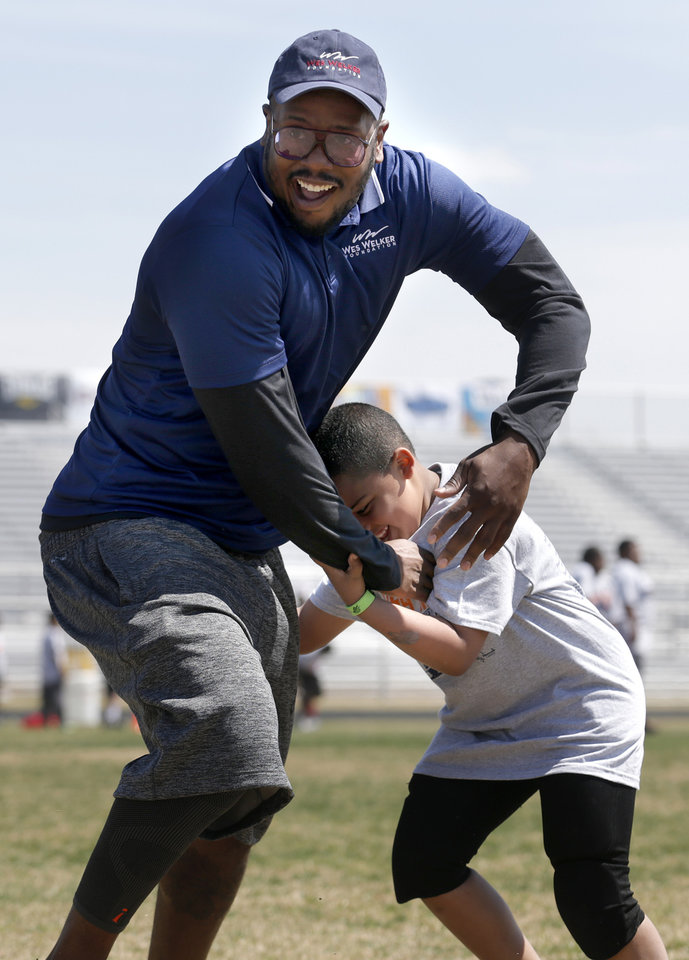 Photo - Denver Broncos'  Von Miller defends against Ronald Graham, 7, during receiving drills at the Wes Welker pro camp at Douglass High School in  Oklahoma City., Saturday, April 05, 2014. Photo by Sarah Phipps, The Oklahoman