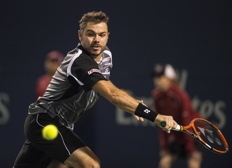 Photo - Stan Wawrinka, of Switzerland, returns the ball to Benoit Paire, of France, during the Rogers Cup men's tennis tournament in Toronto on Tuesday, Aug. 5, 2014. (AP Photo/The Canadian Press, Aaron Vincent Elkaim)