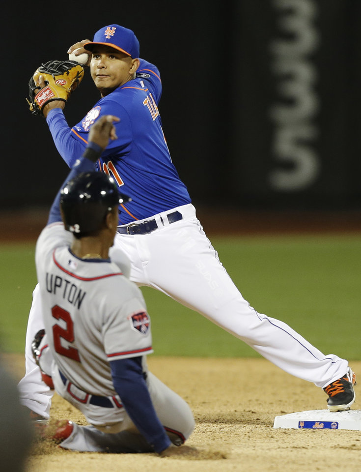 Photo - New York Mets shortstop Ruben Tejada, top, throws out Atlanta Braves' Freddie Freeman at first base after forcing out B.J. Upton (2) for a double play during the third inning of a baseball game on Friday, April 18, 2014, in New York. (AP Photo/Frank Franklin II)
