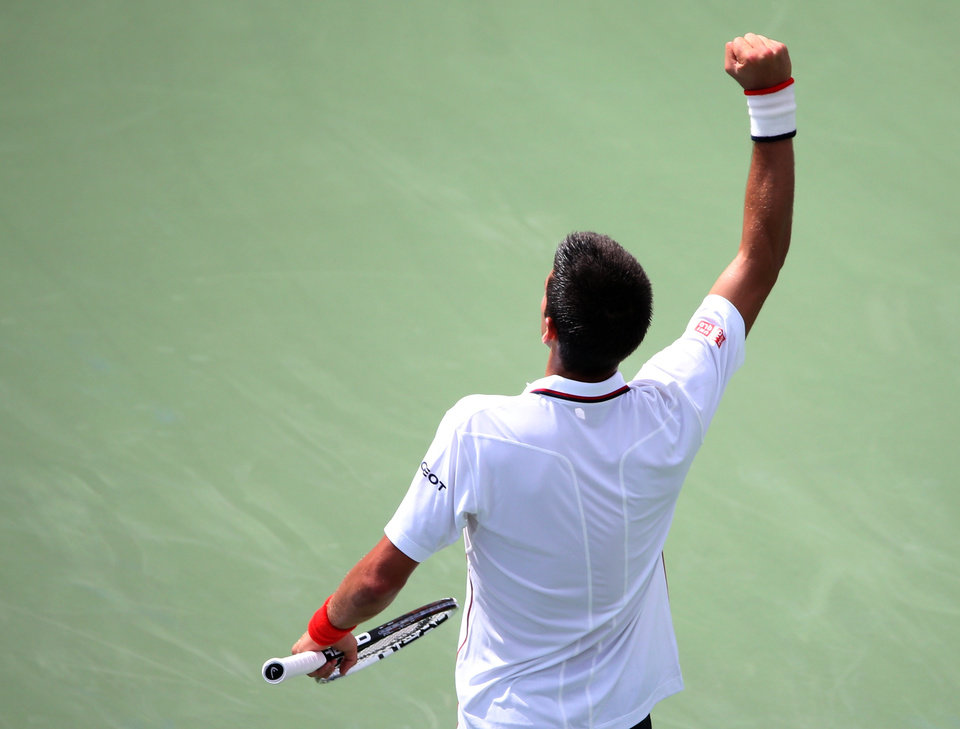 Photo - Novak Djokovic, of Serbia, reacts after a shot against Philipp Kohlschreiber, of Germany, during the fourth round of the 2014 U.S. Open tennis tournament, Monday, Sept. 1, 2014, in New York. (AP Photo/John Minchillo)