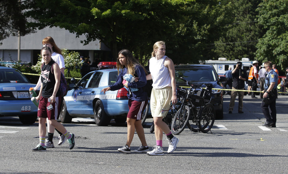 Photo - Students help each other as they walk away from the scene of a shooting Thursday, June 5, 2014, at Seattle Pacific University in Seattle. Police say a university student on Thursday disarmed a lone gunman who entered a building and shot four people. A hospital spokeswoman says one man has died and three other people are injured, one critically. (AP Photo/Ted S. Warren)
