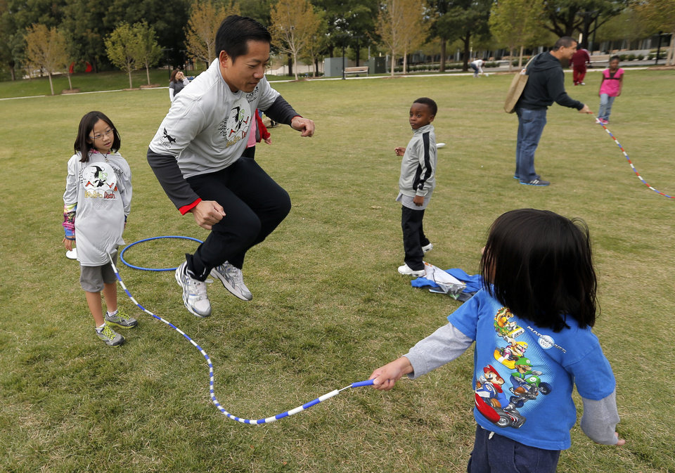 Photo - Hamilton Le jumps rope with his children Jasmyne, 9, left, and Austin, 6, during the YMCA 5210 event Sunday at Myriad Gardens in Oklahoma City.  Photo by Sarah Phipps, The Oklahoman