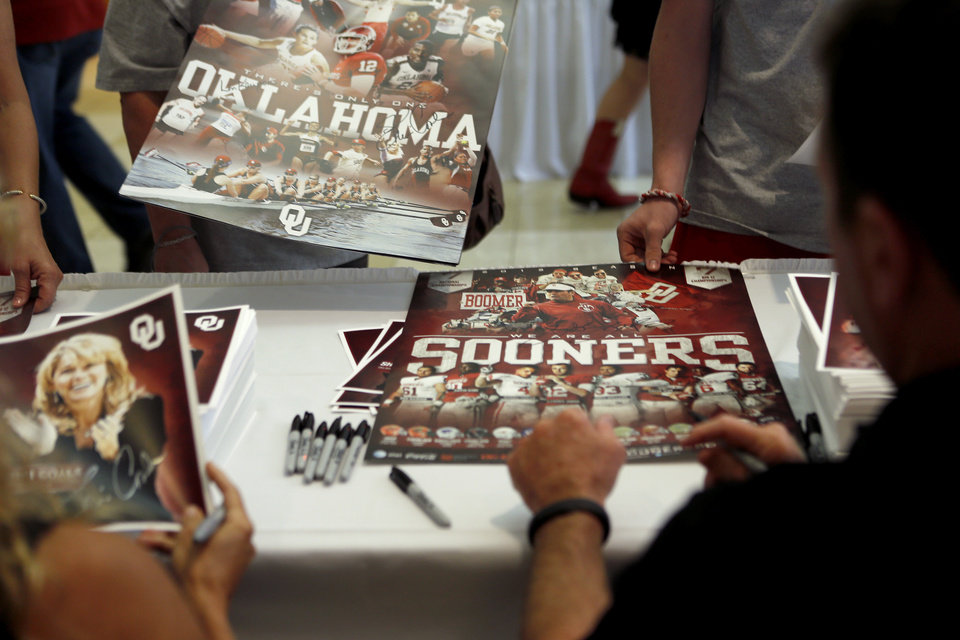 Oklahoma football coach Bob Stoops, right, and women\'s basketball coach Sherri Coale, sign posters for fans during the Sooner Caravan stop at the National Cowboy & Western Heritage Museum in Oklahoma City, Wednesday, August 1, 2012. Photo by Bryan Terry, The Oklahoman