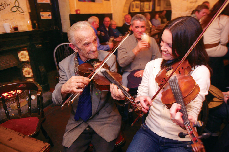 Photo - This undated image provided by the Northern Ireland Tourism Board shows performers playing traditional Irish music at Kelly's Cellars in Belfast, Northern Ireland. It'll cost you to have a pint, of course, but you can enjoy the music for free. It's one of a number of places around Belfast to experience good conversation and music.  (AP Photo/NITB)