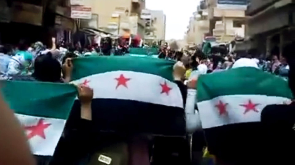 Photo -   This image made from amateur video released by the Ugarit News and accessed Thursday, April 12, 2012, purports to show Syrians holding Syrian revolutionary flags during a demonstration in Deir el-Zour, Syria. A fragile cease-fire brokered by the U.N. took hold in Syria on Thursday with regime forces apparently halting widespread attacks on the opposition. But there were reports of scattered violence and the government defied demands to pull troops back to barracks. The government met demonstrations with a harsh crackdown, and more than 9,000 people have died since the beginning of the revolution, according to the U.N. (AP Photo/Ugarit News via AP video) TV OUT, THE ASSOCIATED PRESS CANNOT INDEPENDENTLY VERIFY THE CONTENT, DATE, LOCATION OR AUTHENTICITY OF THIS MATERIAL