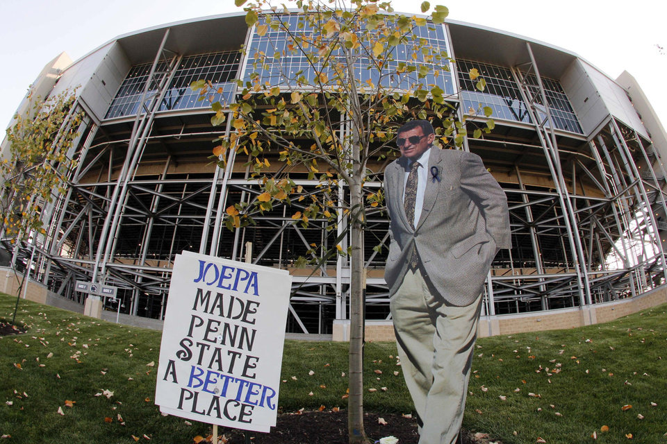 FILE - This Aug. 31, 2012 file photo made with a fisheye lens, shows a cardboard cutout of former Penn State head football coach Joe Paterno outside Beaver Stadium on Penn State's main campus in State College, Pa. The bronzed statue outside Beaver Stadium is gone. The record of 409 career victories erased by the NCAA. But reminders of the late coach Paterno still abound on Penn State football game days. (AP Photo/Gene J. Puskar, File)