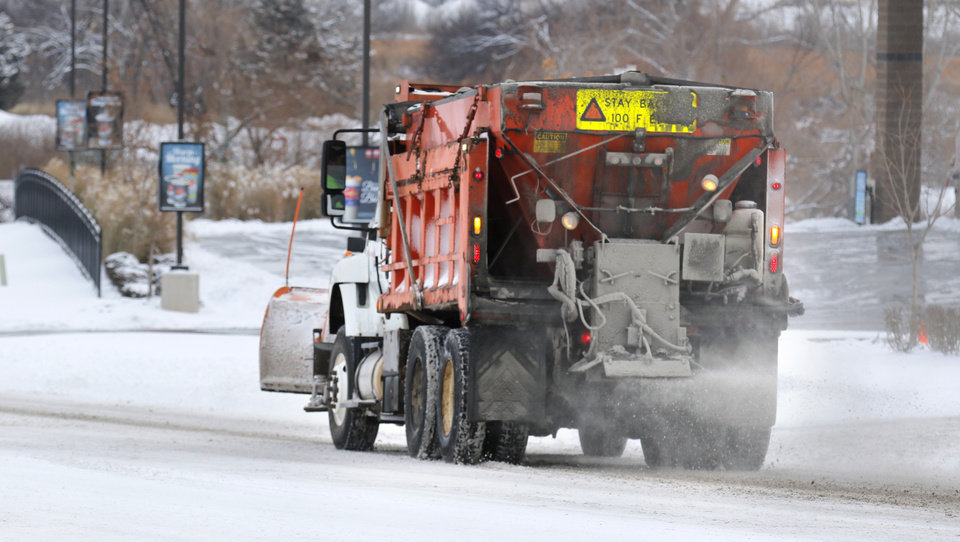 Photo - A snow plow spreads salt on NW 10th street in Yukon, Friday January, 6 2017. Photo By Steve Gooch, The Oklahoman