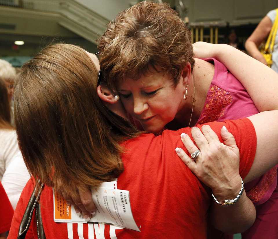 Photo - Moore Public Schools superintendent Susan Pierce, right, gets a hug from Jessica Parker, a teacher at Kingsgate Elementary, after a district-wide meeting of Moore Public Schools employees at Southern Hills Baptist Church, 8601 Pennsylvania Ave., in Oklahoma City, Wednesday, May 22, 2013, after a tornado struck south Oklahoma City and Moore, Okla., on Monday. Photo by Nate Billings, The Oklahoman