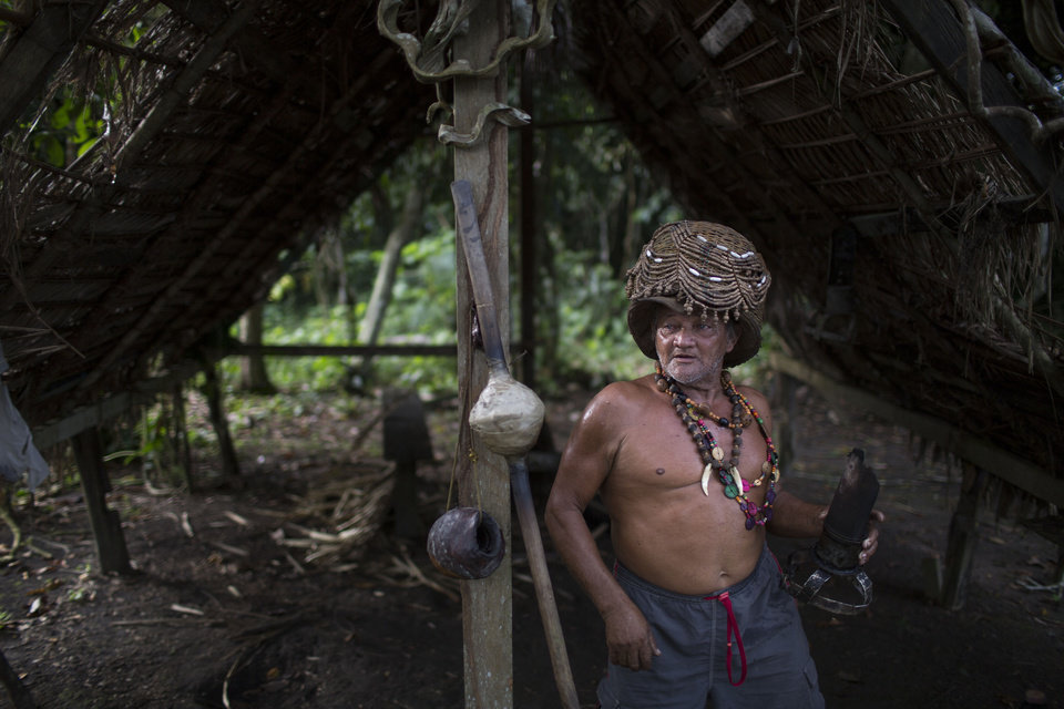 Photo - In this May 23, 2014 photo, Severino Capirava walks in his thatched-roof rubber workshop, near his house in Puraquequara lake, near Manaus, Brazil. Capirava says when harvesting rubber, he wears a variety of amulets and other objects as protection from the harmful elements of the rainforest. (AP Photo/Felipe Dana)