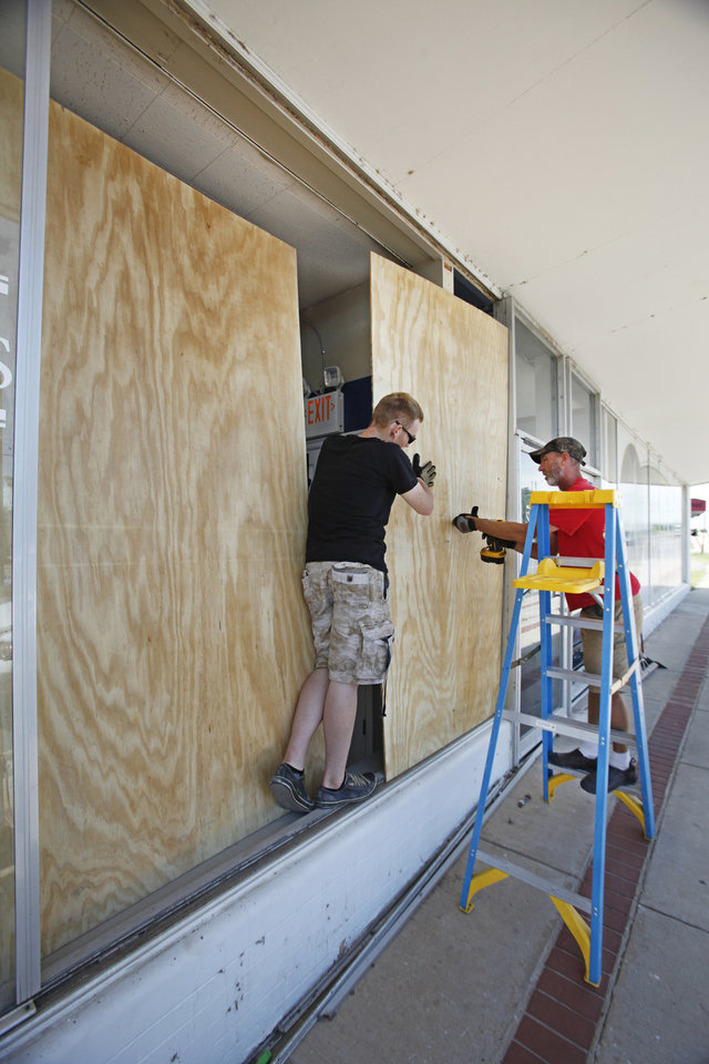 Photo -  Geoff Hampton and Larry Copeland board up a window at Shapes Fitness center that was broken during an early Tuesday earthquake in Harrah. Photo by David McDaniel, The Oklahoman   David McDaniel