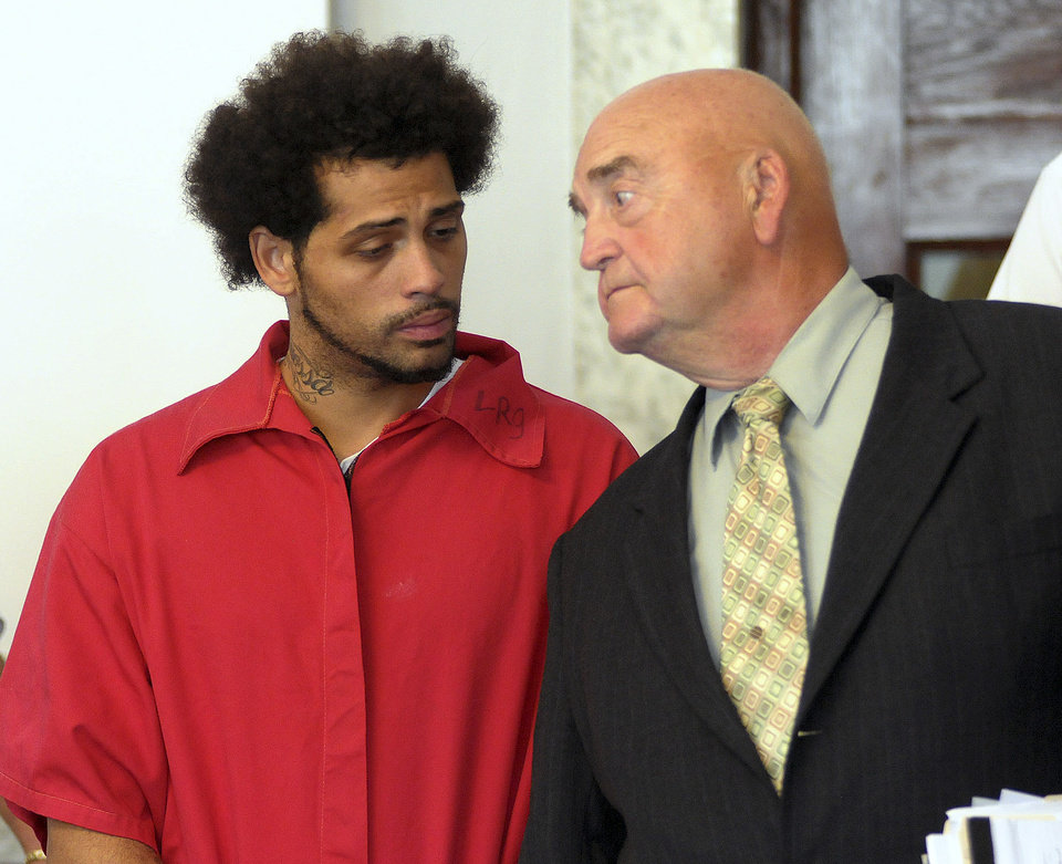 Photo - Carlos Ortiz, left, stands in Attleboro District Court with attorney John Connors, right, for his arraignment on weapons charges, Friday, June 28, 2013 in Attleboro, Mass. Ortiz was arrested Wednesday in Bristol, Conn., in connection with the murder case against former New England Patriots tight end Aaron Hernandez , now charged in the murder of Odin Lloyd.   (AP Photo/The Sun Chronicle, Mark Stockwell, Pool)