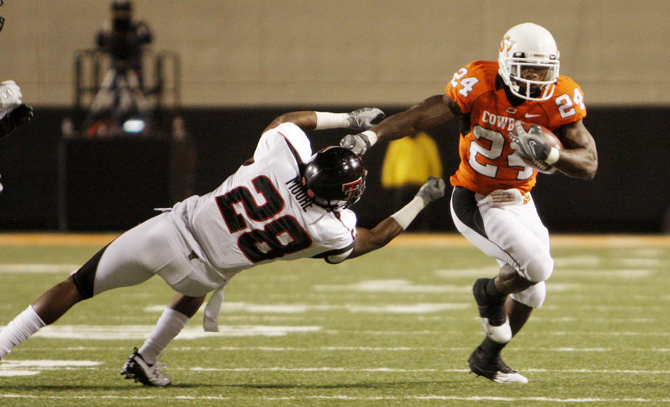 Photo - Cowboy Kendal Huter (24) knocks away LeBron Moore (28) during the college football game between Oklahoma State University (OSU) and Texas Tech University at Boone Pickens Stadium in Stillwater, Okla. Saturday, Nov. 14, 2009. Photo by Doug Hoke, The Oklahoman