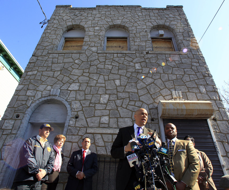 Photo -   Newark Mayor Cory Booker stands in front of a boarded-up 433 Hawthorne Avenue in Newark, N.J., Friday, April 13, 2012 as he talks about rescuing a neighbor Thursday from a fire at the home. Boooker said Friday he feared for his life as he helped rescue a neighbor from a fire before firefighters arrived. Booker described how he returned home Thursday night and saw his neighbor's home engulfed in flames. The woman Booker helped save is in stable condition. (AP Photo/Mel Evans)