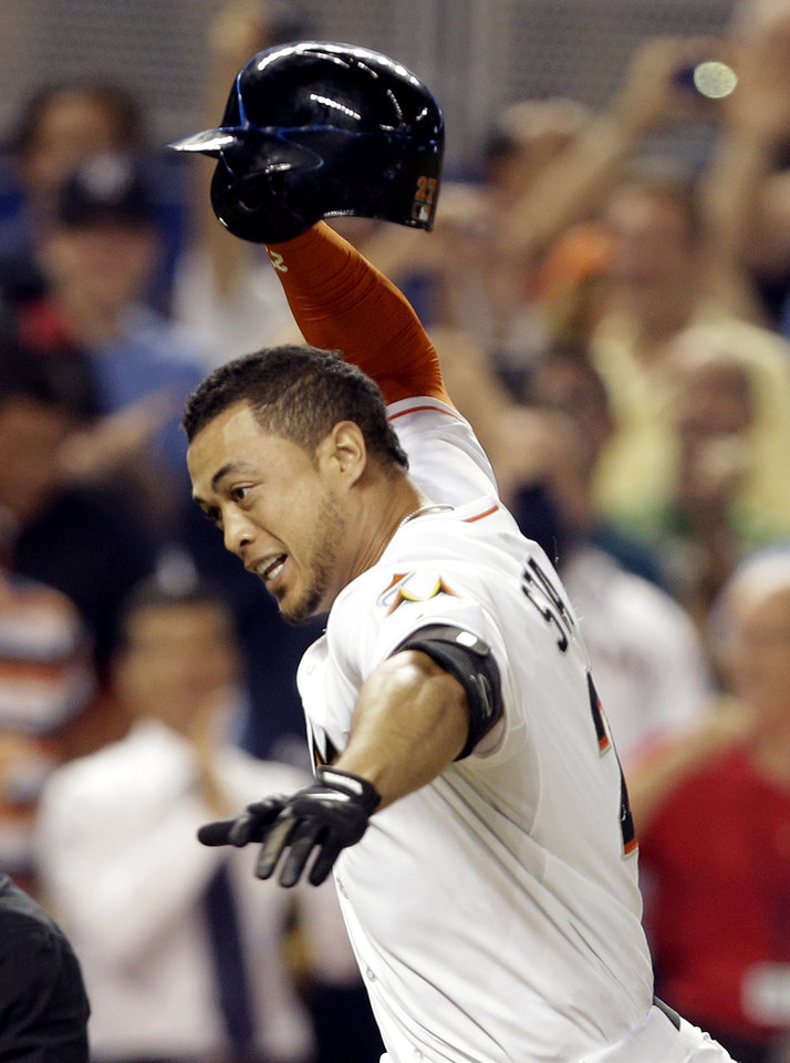 Photo - Miami Marlins' Giancarlo Stanton runs to home plate after hitting a grand slam to defeat the Seattle Mariners 8-4 during the ninth inning of an interleague baseball game, Friday, April 18, 2014, in Miami. (AP Photo/Lynne Sladky)