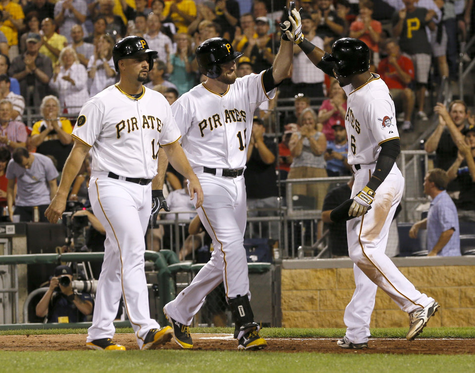 Photo - Pittsburgh Pirates' Ike Davis (15) is greeted by teammates Gaby Sanchez, left, and Starling Marte after driving them in with a three-run home run n the eighth inning of the baseball game against the St. Louis Cardinalson Tuesday, Aug. 26, 2014, in Pittsburgh. The Pirates won 5-2. (AP Photo/Keith Srakocic)
