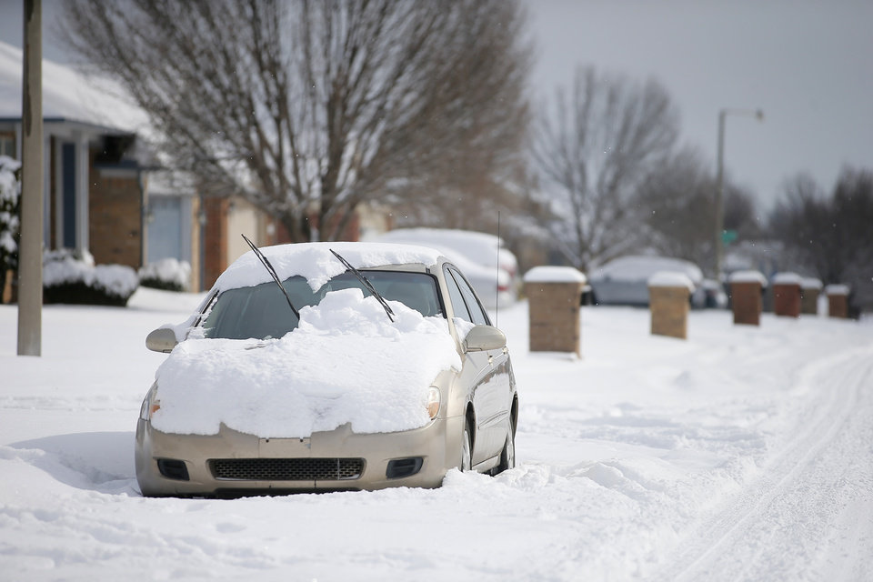 Photo - A car covered in snow is parked on the street in northwest Oklahoma City after a winter storm dropped another layer of snow in Oklahoma City, Wednesday, Feb. 17, 2021. [Bryan Terry/The Oklahoman]