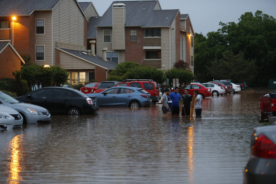 Photo - A group stands in a flooded parking lot of an apartment complex at NW 30th and Villa as heavy rain moved into Oklahoma City, Saturday, May 23, 2015. Photo by Sarah Phipps, The Oklahoman