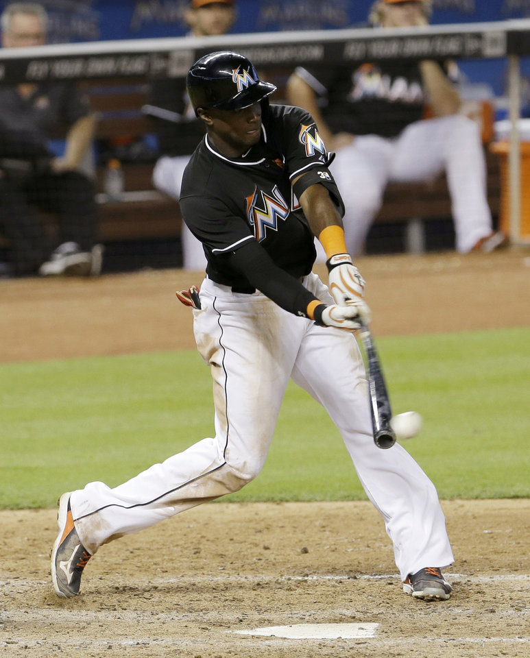 Photo - Miami Marlins' Adeiny Hechavarria hits a single against the Pittsburgh Pirates in the ninth inning of a baseball game in Miami, Saturday, June 14, 2014. The Pirates won 8-6. (AP Photo/Alan Diaz)