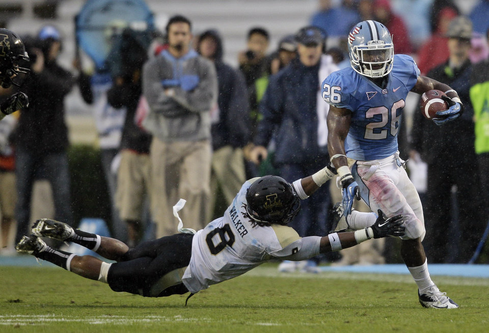 North Carolina's Giovani Bernard (26) breaks a tackle against Idaho's Gary Walker (8) during the first half of an NCAA college football game in Chapel Hill, N.C., Saturday, Sept. 29, 2012. (AP Photo/Gerry Broome)
