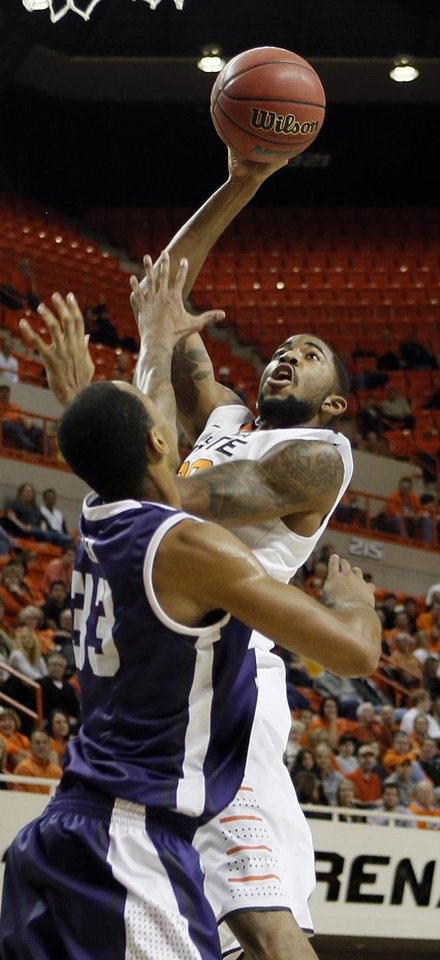 Photo - Oklahoma State's Michael Cobbins (20) shoots boer TCU's Garlon Green (33) during the college basketball game between Oklahoma State University Cowboys (OSU) and Texas Christian University Horned Frogs (TCU) at Gallagher-Iba Arena on Wednesday Jan. 9, 2013, in Stillwater, Okla. 
