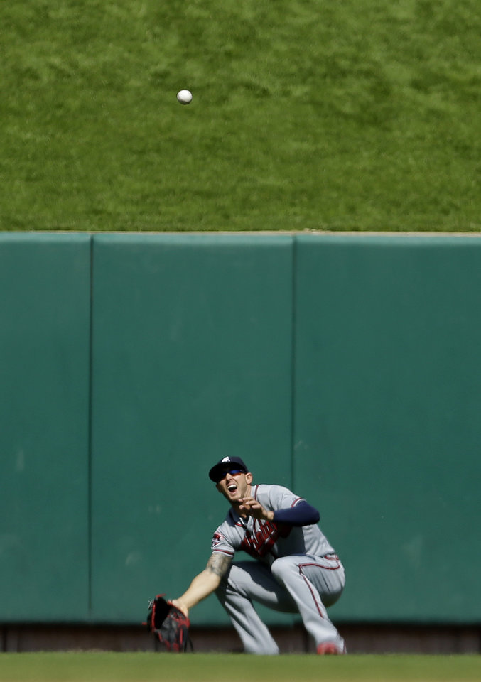 Photo - Atlanta Braves center fielder Jordan Schafer looks for a ball after losing it in the sun as it drops in for a double by St. Louis Cardinals' Jhonny Peralta during the seventh inning of a baseball game Sunday, May 18, 2014, in St. Louis. The Cardinals' Yadier Molina scored on the play. (AP Photo/Jeff Roberson)