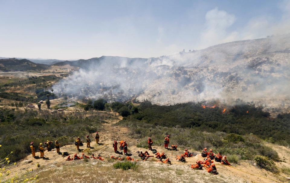Photo - Firefighters take a break on a hillside after hours of work as the brush burns below them Thursday, May 15, 2014, in San Marcos, Calif. Gusty winds failed to return Thursday morning in San Diego County wildfire areas and authorities said it was a window of opportunity to make further gains against flames that burned homes and drove tens of thousands from their homes. (AP Photo)